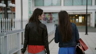 Happy young women friends walking over the bridge with shopping bags, talking discuss, back view, slow mo stedicam shot