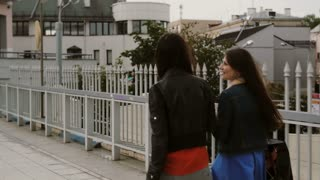 Happy young women friends walking over the bridge with shopping bags, talking discuss, back view, stedicam shot 4K
