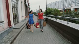 Happy young women friends walking with shopping bags, talking discuss having fun. slow mo stedicam shot