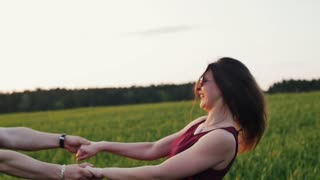Joyful lovers swirl around in nature. Pretty couple hug and kiss expressing love. Sunset light. Slow mo, steadicam shot
