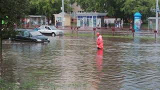 JULY 20 2016 MINSK, BELARUS broken cars are on the road after flood with sound. Road worker in overalls