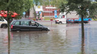 JULY 20 2016 MINSK, BELARUS Flood on a busy road in the city streets after rain. broken car standing amidst the water