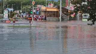 JULY 20 2016 MINSK, BELARUS Flood on busy road in city streets after rain with sound. Crowd of people stand and wait.