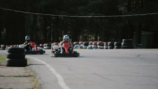 Kart drivers moving on a go kart track passing by the camera.