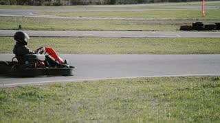 Kart drivers moving on a go kart track.