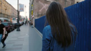 Lady walks in the street near blue fence. Backview of woman with long hair talking on the phone. Slow mo, steadicam shot