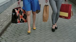 legs slender young girls walking down the street past the store with shopping bags, slow mo stedicam shot