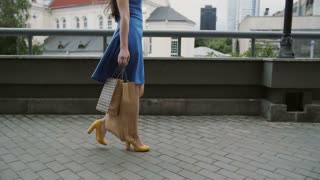 legs slender young woman, walking in the city down the street with shopping bags, side view, slow mo, stedicam shot