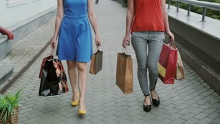 legs slender young women walking down the street past the store with shopping bags, slow mo stedicam shot