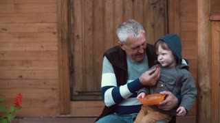 Little boy in the hood sitting on grandfather lap and eating berries from the orange bowl. Old man feeding grandson. 4K