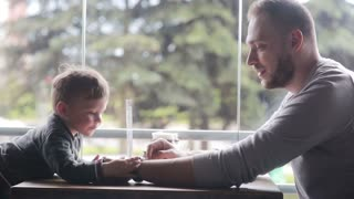 little boy looks at smartclock on father's hand