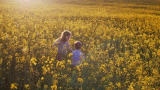 Little girl and boy in a field at sunset. Slow mo