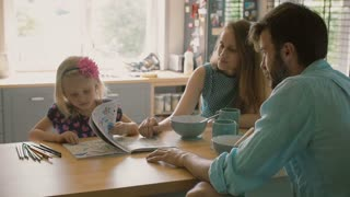Little girl is showing her colouring book to her parentswhile they are having breakfast at the kitchen table. Slow mo