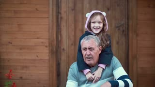 Little girl standing behind old man. Granddaughter hug grandfather, embracing shoulders. Female smiling and laughing. 4K