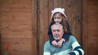 Little girl standing behind old man. Granddaughter hugs grandfather, grandson running to they. Boy sits on man knees. 4K