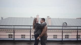 Love in the city. Happy man lifts his beloved in his arms and swirls around on a roof. Woman is happily smiling.