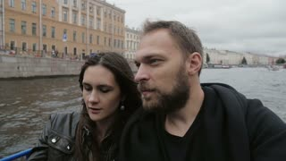 Lovers enjoy a city view on a tour in St Petersburg, taking selfie. Going under a bridge, light goes off and on, slow mo