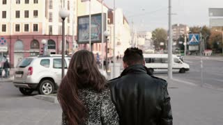 Lovers in the city. Beautiful girl looks back in camera, leans on her mans shoulder. Back view, slow mo, steadicam shot