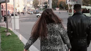 Lovers walk in the street. Handsome stylish man with a beard looks back in camera. Back view, slow mo, steadicam shot