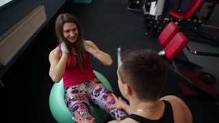 Lovers work out together. Woman giving her man a kiss while doing press exercises. He helps her. Working out in the gym.