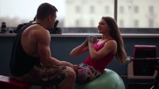 Lovers work out together. Woman giving her man kisses while doing press exercises. He helps her. Working out in the gym.