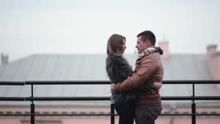 Loving couple kiss and laugh standing on a roof in cold weather. They hug each other, girl in a fur coat, side view