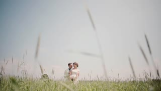 Loving couple standing close to each other in wheat field on their wedding day, Bride and groom in wedding outfits