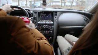 Man and woman sitting in a car while driving. Man is drinking some beverage. Black dashboard of a car. Traveling by car.