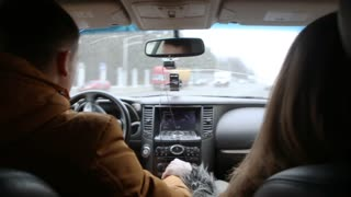 Man and woman talking in a car while driving. Man turns right. Traveling by car.