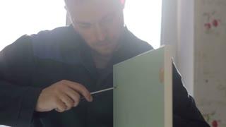 man assembles furniture using a screwdriver