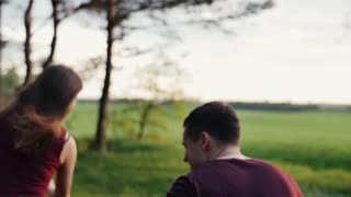 Man chases his woman cheerfully running in a field. Happy lovers have fun. Soft sunset lights. slow mo, steadicam shot