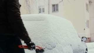 man clears snow from his car on the street in winter, back view,