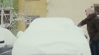 man clears snow from his car on the street in winter, front view, time lapse,