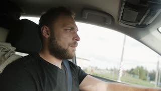 Man driving a car. Handsome man with a beard in a black T-shirt drives his car. Traveling by car.