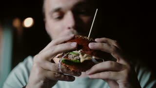 man enjoys eating, tasting the delicious big burger meat with cheese and vegetables
