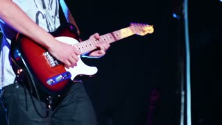 Man hands playing electric guitar at the concert