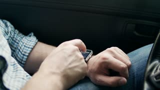 Man hands using smart watch sitting in car