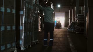 Man in uniform works in a warehouse. Loader transports palettes with load on it. Packages on the shelves