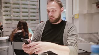 Man is being irritated. Man does not like his smartphone. Man holds a smartphone in his hand. Modern technology.