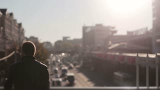 Man looks at traffic in the city in the sunset