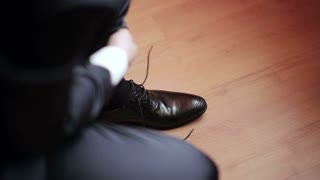 Man tying patent leather shoes