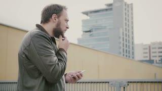 Man using his smartphone standing on the roof, then walks away. hands closeup. 4k