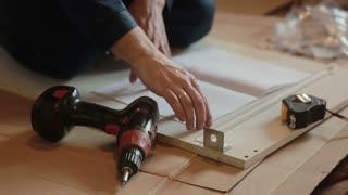 man worker assembles furniture using instruction