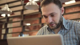 Man working on modern laptop in cafe