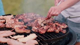 Mans cooking chicken on barbecue grill outdoor. The smoke coming from the barbecue grill.