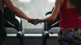 Men and women train in the gym holding hands