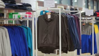 Middle-aged man chooses a jacket in store