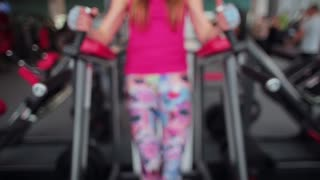Midsection of a woman exercising legs while doing I-sits on parallel bar in a sport club. Workout in a gym