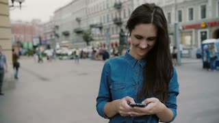 Modern technology. Smiling young woman in a denim dress using her smartphone in a busy street. Slow mo, steadicam shot