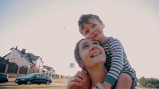 Mom and her little son are happy together on a sunny day. Cute little boy sits on his moms shoulders. Slow mo